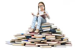 Portrait of cute girl sitting on pile of books and looking at camera Stock Photos