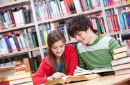 Stock Photo of portrait of teenage girl reading book with her classmate near by