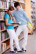 portrait of teenage girl reading book in library with her classmate near by - stock photo