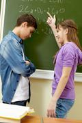clever girl pointing at blackboard while explaining formula to classmate - stock photo