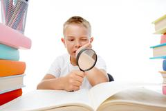 Smart youth reading open book before him with serious facial expression Stock Photos