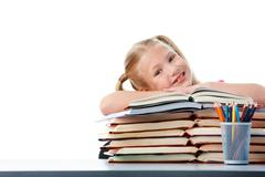 Portrait of cute schoolgirl keeping her arms on open books and looking at camera Stock Photos