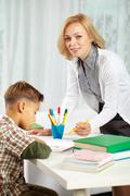 portrait of pretty tutor looking at camera with diligent boy sitting near by - stock photo