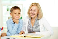 portrait of pretty tutor and diligent pupil looking at camera with smiles - stock photo