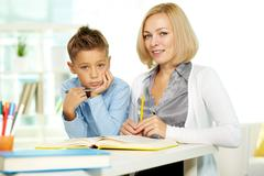 portrait of pretty tutor and diligent pupil looking at camera - stock photo