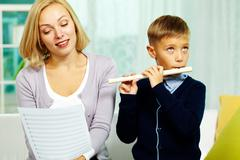 Portrait of happy pupil playing the flute with charming tutor near by Stock Photos