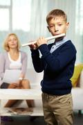 Portrait of cute boy playing the flute with tutor on background Stock Photos