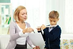 portrait of pupil playing the flute while his tutor showing notes - stock photo