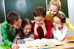 Portrait of friendly group reading book in classroom Stock Photos
