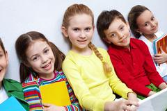 Portrait of five pupils looking at camera while sitting on the floor Stock Photos