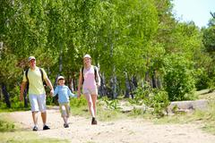 Portrait of three family members walking down road at summer Stock Photos