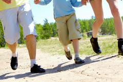 Legs of three family members going down forest path during summer vacation Stock Photos
