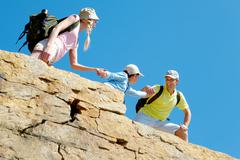 Portrait of happy man helping his wife and son to climb onto high rock Stock Photos