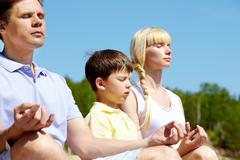 Photo of three family members meditating on summer day outdoors Stock Photos