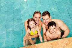 photo of happy family in swimming pool smiling at camera - stock photo