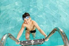 Photo of happy lad in pool smiling at camera Stock Photos
