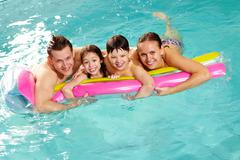 Cheerful family in swimming pool having nice time Stock Photos