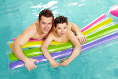 photo of happy lad and his father in water - stock photo