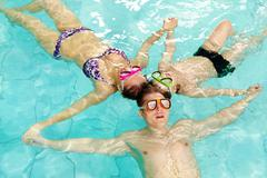 photo of parents and their son in goggles holding by hands in water - stock photo