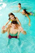 Photo of happy girl sitting on her father shoulders in pool with swimming boy an Stock Photos