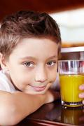 portrait of cute lad with glass of juice looking at camera in cafe - stock photo