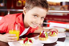 Portrait of cute lad with glass of juice and tasty cupcakes in cafe Stock Photos