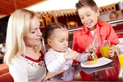 Portrait of cute girl eating cupcake with her mother and brother near by in cafe Stock Photos
