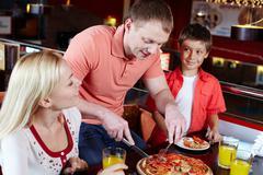 portrait of happy family spending time in pizzeria - stock photo