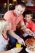 portrait of happy family having lunch in pizzeria - stock photo