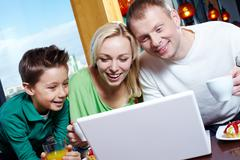 Image of happy family looking at laptop screen in cafe Stock Photos