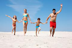 Photo of happy family running down sand on summer vacation Stock Photos