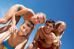photo of happy family looking at camera during summer vacation - stock photo