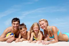 photo of happy family lying on sand on background of blue sky - stock photo