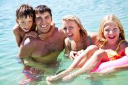 Stock Photo of portrait of cheerful family looking at camera from water