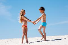 Photo of happy siblings on sand having nice summer vacation Stock Photos