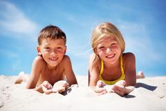 Photo of happy siblings lying on beach and playing with sand on summer vacation Stock Photos