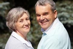 Portrait of happy senior couple looking at camera on sunny day Stock Photos