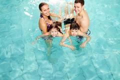Photo of happy family in swimming pool smiling at camera Stock Photos