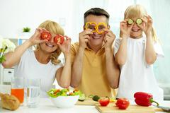 portrait of happy parents and their daughter posing with vegetables in the kitch - stock photo