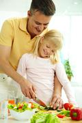 Portrait of happy father and daughter cooking vegetable salad in the kitchen Stock Photos