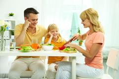 Portrait of pretty woman cooking salad while her husband and daughter looking at Stock Photos