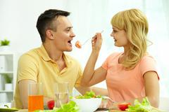 image of woman giving her husband slice of tomato on fork - stock photo