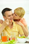 Image of woman kissing her husband while he eating salad Stock Photos