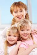 a young family of woman and twin sisters looking at camera - stock photo