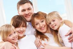 Stock Photo of a young friendly family looking at camera