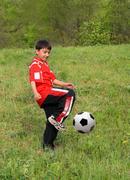 Asian boy playing football Stock Photos