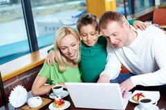 Image of happy family looking at laptop screen in cafe Kuvituskuvat