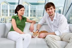 A young couple sitting on sofa with a cat and looking at camera Stock Photos