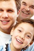 close-up of a boy's face looking at camera among his father and grandfather - stock photo