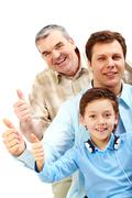 portrait of a man, older man and boy showing big thumb - stock photo
